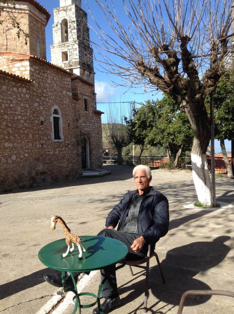 Socrates sits with Ithomi outside his bar in the small square of Vorio