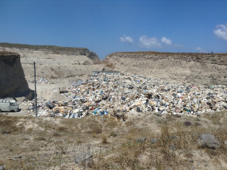 A rubbish tip in Santorini, just next to the main road outside Fira, it is an open dump site and all around the rubbish is blown by the wind