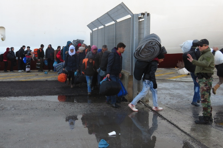 Lines of refugees make their way towards the ferry in Lesbos